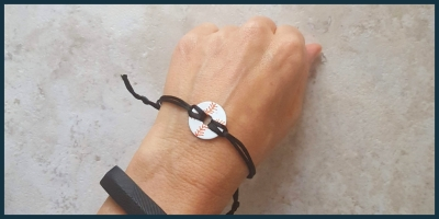 A bracelet made from a washer painted to look like a baseball